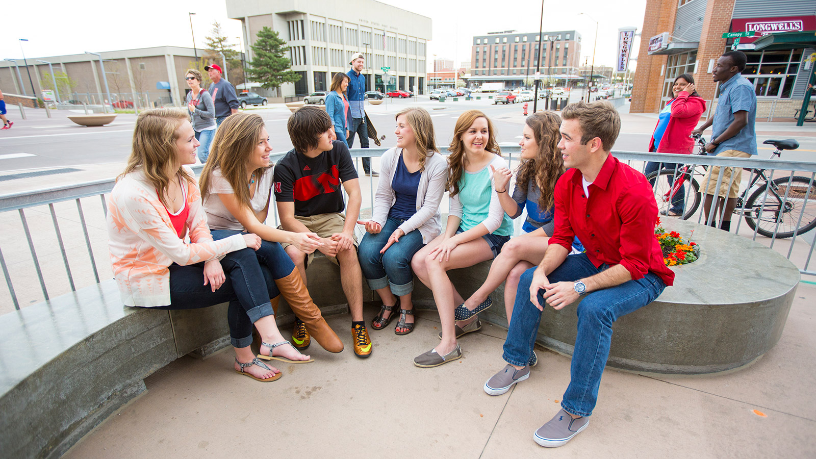 A group of students sitting outside in downtown Lincoln talking.